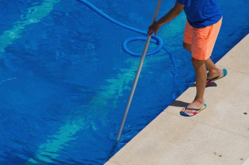 Cleaning pool walls and tiles in a Mesquite home.